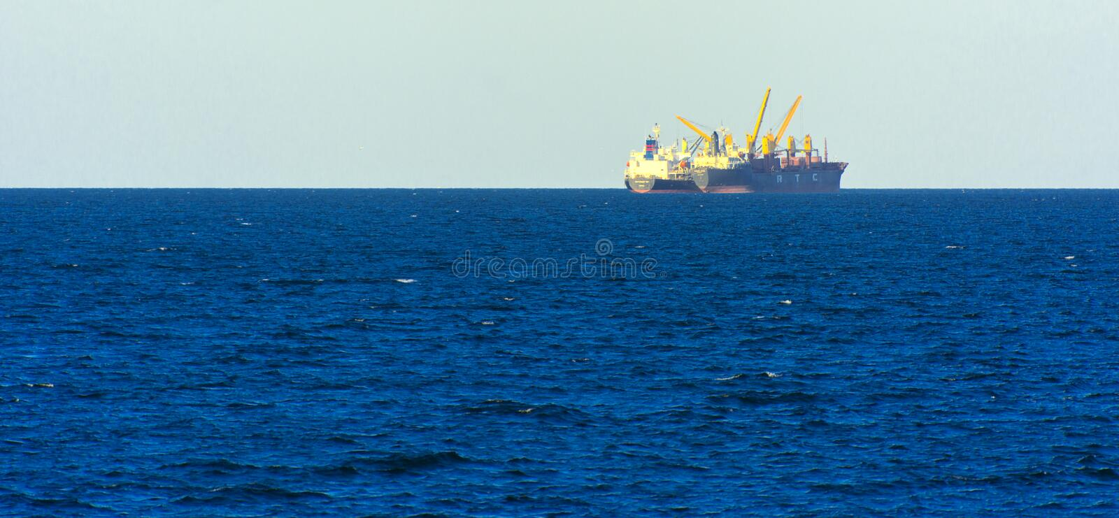Odessa, Ukraine - August 08, 2018. A large cargo ship transports. Containers in the open sea in the evening soft sunlight against a blue sky. The concept of stock photography