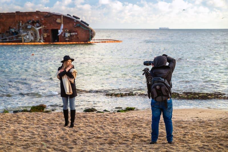 Odessa, Ukraine, December 2019: Photographer teen taking photos of female model on beach at sunset. Photo session royalty free stock photo