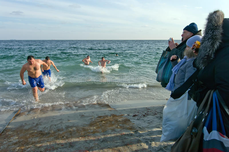 Odessa, Ukraine JANUARY 19, 2012: --:Peopls swimming in ice cold water Black Sea during Epiphany (Holy Baptism) in the O royalty free stock photos