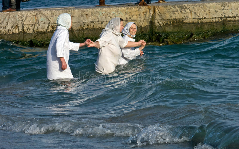 Odessa, Ukraine JANUARY 19, 2012: --:Peopls swimming in ice cold water Black Sea during Epiphany (Holy Baptism) stock photography