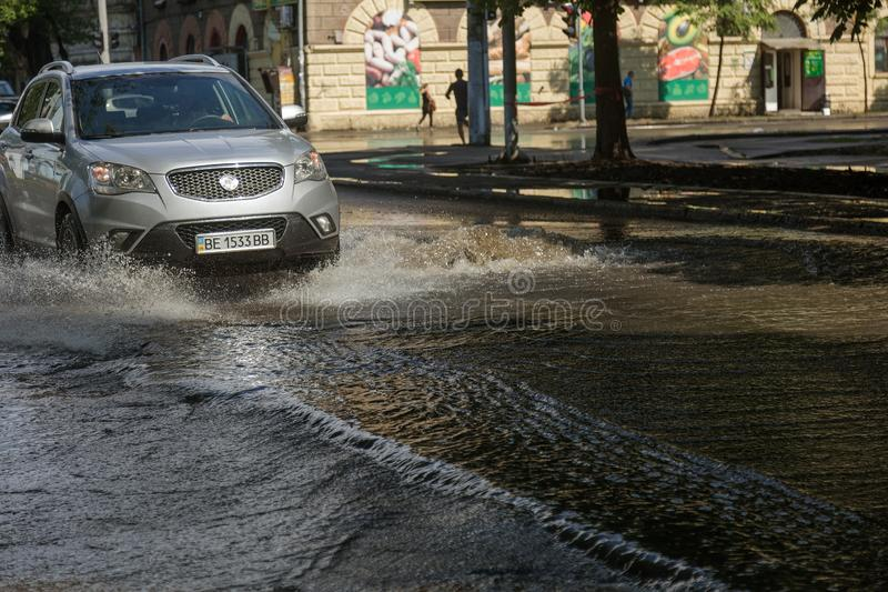 Odessa, Ukraine -3 July 2018: Driving cars on a flooded road during floods caused by rain storms. Cars float on water, flooding st. Reets. Splash on the machine stock image