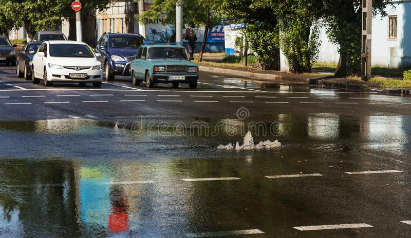 Odessa, Ukraine -3 July 2018: Driving cars on a flooded road during floods caused by rain storms. Cars float on water, flooding st. Reets. Splash on the machine stock photography