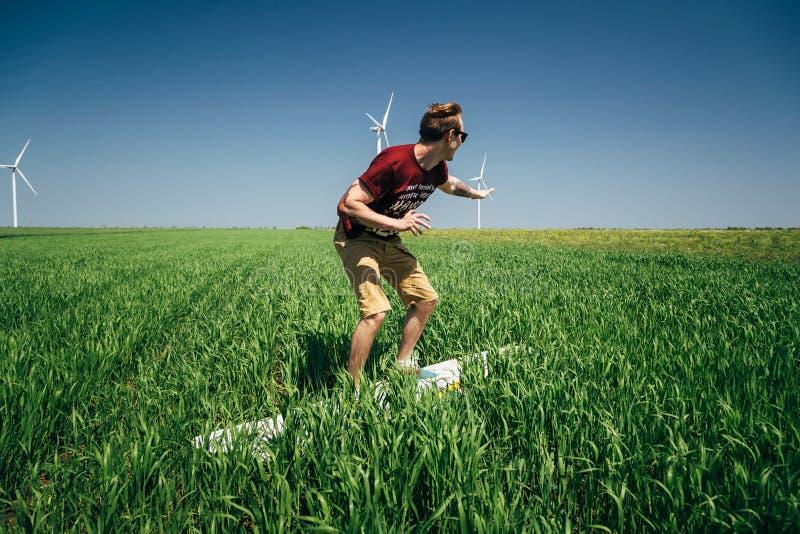ODESSA, UKRAINE -, 20 KANN 2015: Junger Hippie-Mannsurfer ist, surfend scherzend und auf dem grünen Gebiet lizenzfreies stockbild