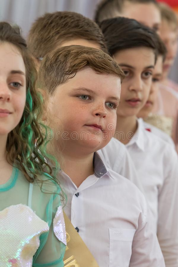 Odessa, Ukraine - May 31,2018: Children`s musical group sing and. Dance on stage during graduation concert of elementary school. Children play. Emotional stock photography