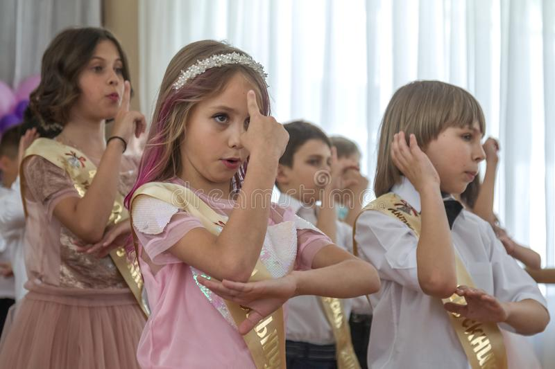 Odessa, Ukraine - May 31,2018: Children`s musical group sing and. Dance on stage during graduation concert of elementary school. Children play. Emotional stock image