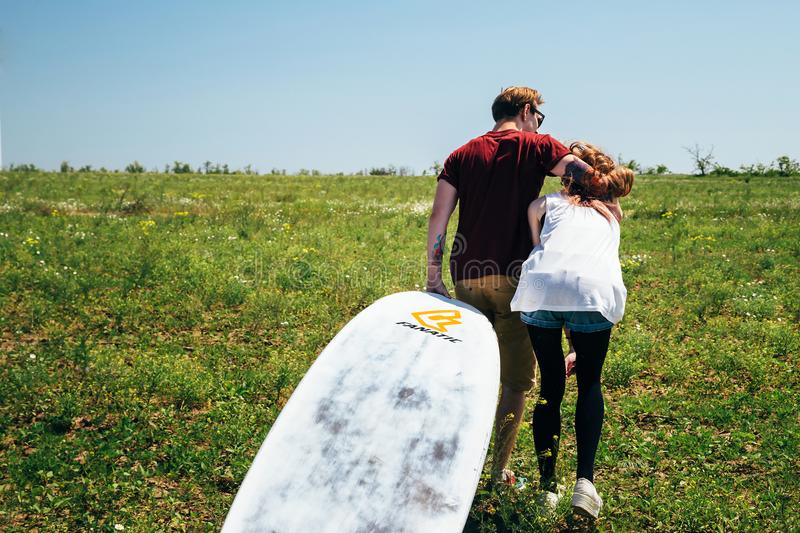 ODESSA, UKRAINE - MAY, 20 2015: Cute young hipster couple of surfers with a surfboard is on the way to the beach. Back view.  royalty free stock image