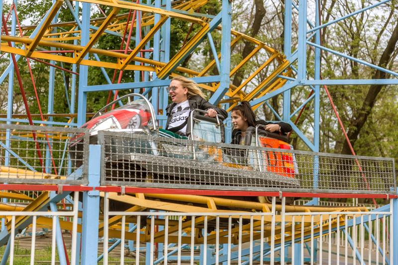 ODESSA, UKRAINE - MAY 6, 2019: Visitors ride road slides in an amusement park. Young friends on an exciting rollercoaster. Young stock photography