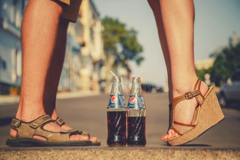 ODESSA, UKRAINE - OCTOBER 15, 2014: Close up of woman feet standing on tiptoe while kissing with man outdoors summertime. Pepsi in stock image