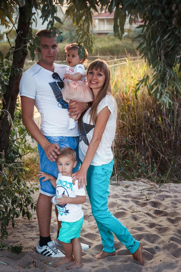 ODESSA, UKRAINE - SEPTEMBER 02, 2014: Young family with their babies outside in the park royalty free stock photos