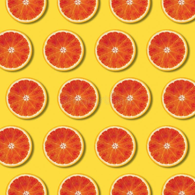 Odgórnego widoku pomarańcze plasterków czerwony wzór na żółtym tle zdjęcia stock