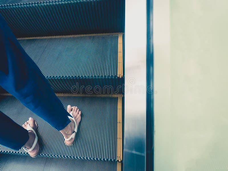 Odgórny puszka widok dorosłej kobiety cieki, widzieć pozycja na sposobie w górę eskalatoru z kopii przestrzenią, fotografia stock
