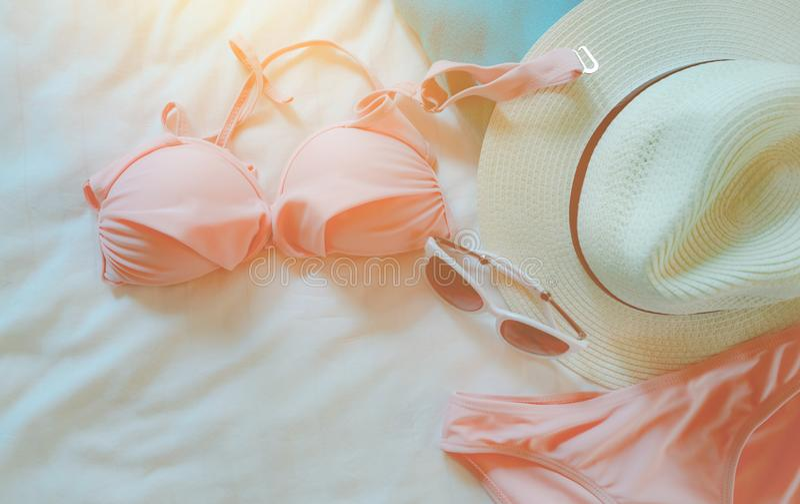 Odgórny widok bikini swimsuit, okulary przeciwsłoneczni i słomiany kapelusz na łóżkowym prześcieradle, Kobiety plaży i swimwear a fotografia stock