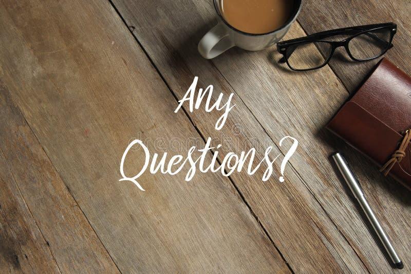 Odgórny widok filiżanka kawy, szkła, notatnik i pióro na drewnianym tle pisać z Jakaś pytaniami, fotografia stock
