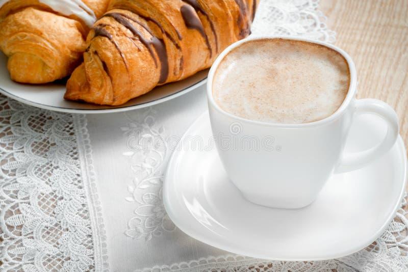 Odgórny widok na filiżanka kawy z mlekiem, croissants na drewnianym stole zdjęcia royalty free