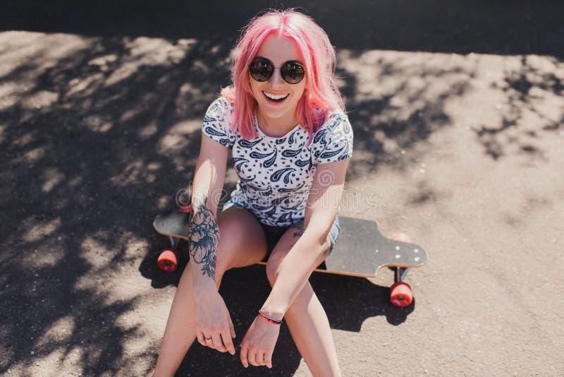 Odgórny widok sporty piękna uśmiechnięta kobieta jest ubranym czarnych okulary przeciwsłonecznych z tatuażem na ręce z różowym wł zdjęcia royalty free