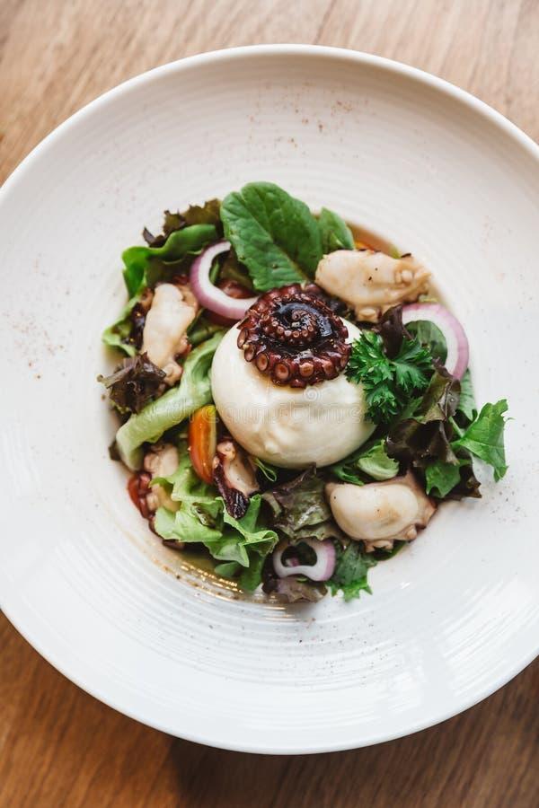 Odgórny widok Uwędzona Galicyjska ośmiornica z Burrata serem, rzodkwią, zielonym dębem i pomidorem, zdjęcie stock