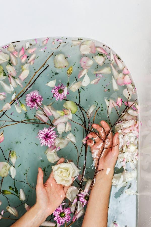 Odgórny widok wypełniający z wodą, kwiatami, gałąź i płatkami z kobiety ręką skąpanie błękitnymi bąbla, obraz stock