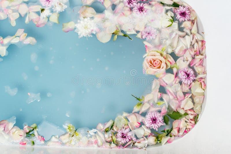 Odgórny widok wypełniający z wodą, kwiatami i płatkami skąpanie błękitnymi bąbla, fotografia stock