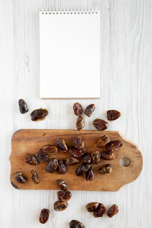 Odgórny widok, wysuszone daty na nieociosanej drewnianej desce, pusty notepad na białej drewnianej powierzchni Od above, koszt st fotografia royalty free