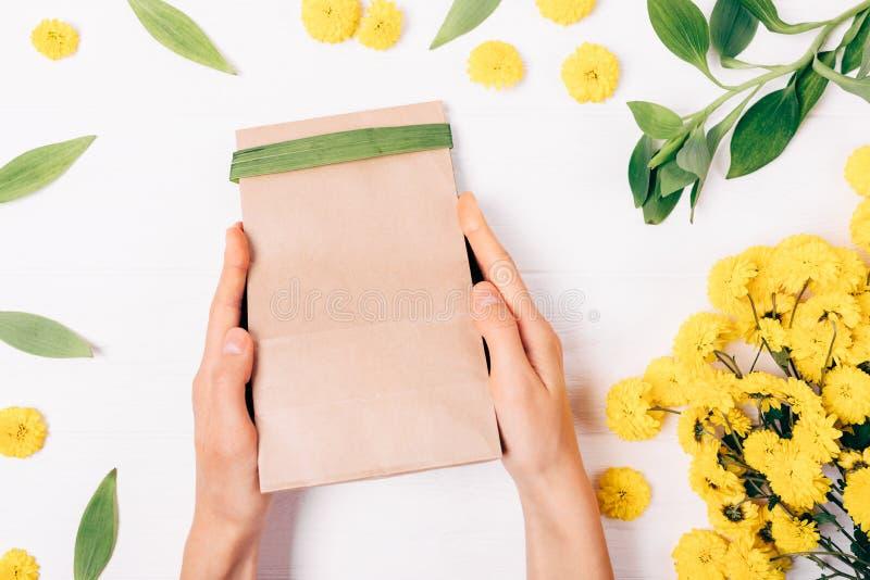 Odgórnego widoku żeńskie ręki trzyma brązu papieru prezent zdosą zdjęcie royalty free