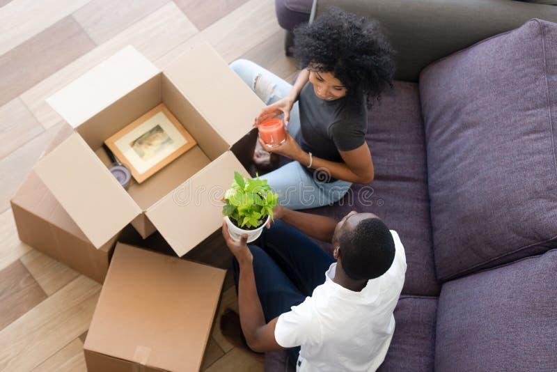 Odgórnego widoku amerykanin afrykańskiego pochodzenia szczęśliwa para w miłości odpakowywa pudełka w domu obrazy royalty free