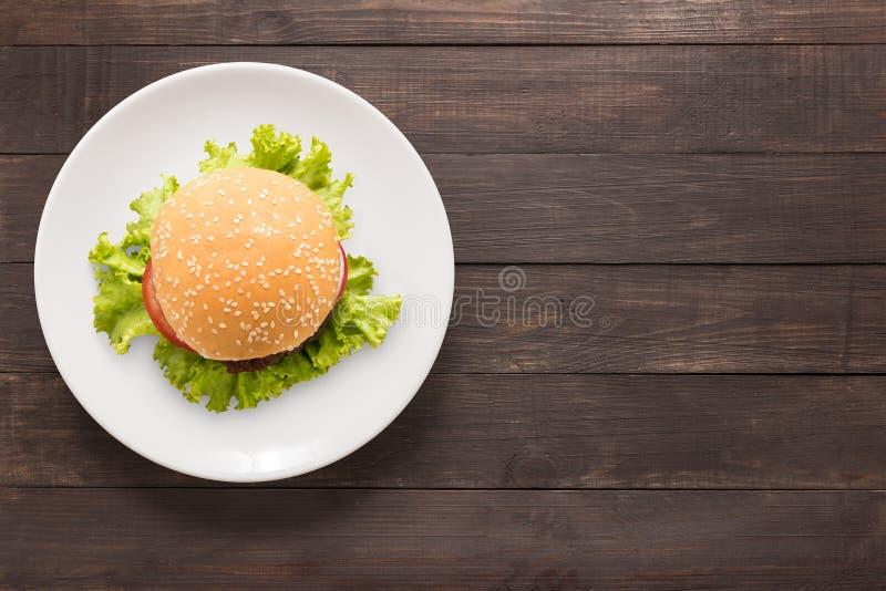 Odgórnego widoku BBQ hamburger na białym naczyniu na drewnianym tle obrazy stock