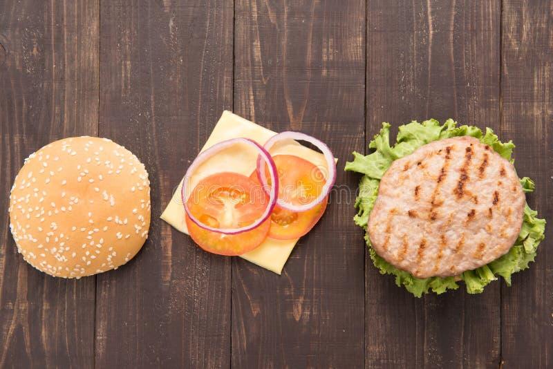 Odgórnego widoku bbq hamburger rozdziela horyzontalnego na drewnianym tle obrazy stock
