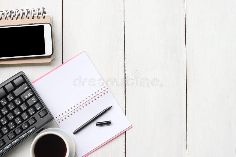 Odgórnego widoku biurka biały drewniany stół z klawiaturowym smartphone suppli zdjęcia royalty free