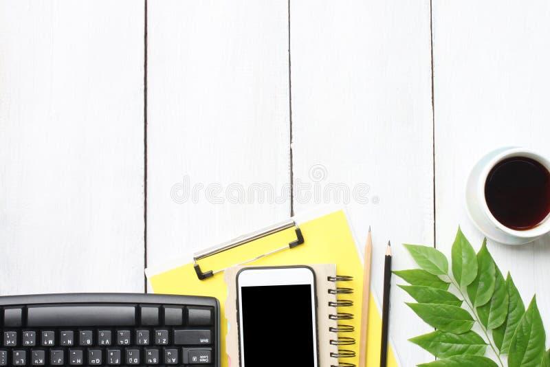 Odgórnego widoku biurka biały drewniany stół z klawiaturowym smartphone suppli obraz stock