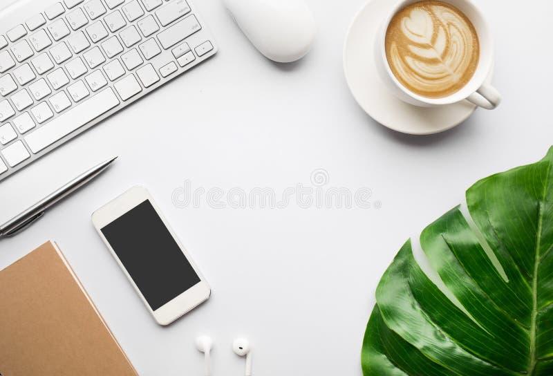 Odgórnego widoku biurowego biurka nowożytny stół z tropikalnymi liśćmi obrazy royalty free