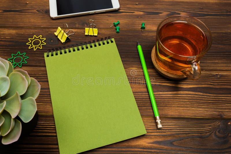 Odgórnego widoku biznesu biurowy biurko notatnik, ołówek, herbaciana filiżanka, roślina, telefon komórkowy, paperclips na drewnia obraz stock