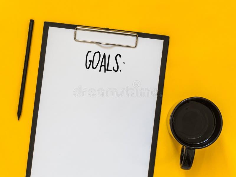 Odgórnego widoku cele spisują z notatnikiem, filiżanka kawy na żółtym backg zdjęcie royalty free
