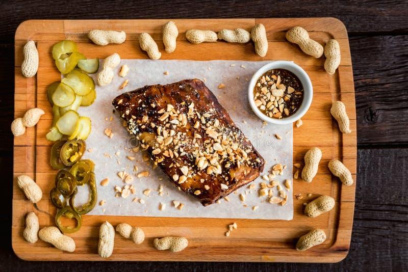Odgórnego widoku deska z wieprzowina ziobro piec na grillu z kumberlandem, arachidami i jalapeno BBQ, fotografia stock