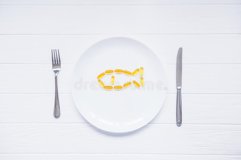 Odgórnego widoku dorsza wątróbki oleju kapsuły, omega 3, witamina d w rybim kształcie na białym round talerzu słuzyć z nożem i ro obrazy royalty free