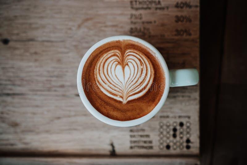 Odgórnego widoku latte sztuki kawa na drewnianym stole Zamyka up z odbitkowym zdrojem obraz stock