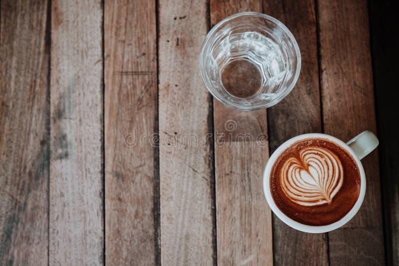 Odgórnego widoku latte sztuki woda na drewnianym stole i kawa Zamyka w górę dowcipu obraz royalty free
