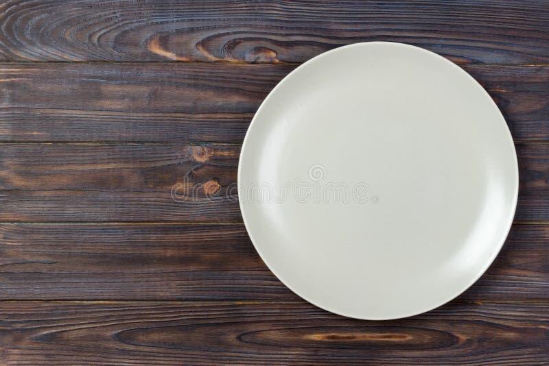 Odgórnego widoku matte pusty talerz na nieociosanym drewnianym stole Odgórny widok zdjęcia royalty free