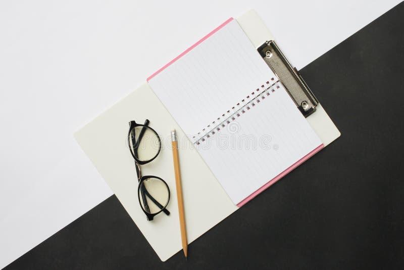 Odgórnego widoku notatników ołówki i szkła umieszczający na whi i czerni zdjęcie stock