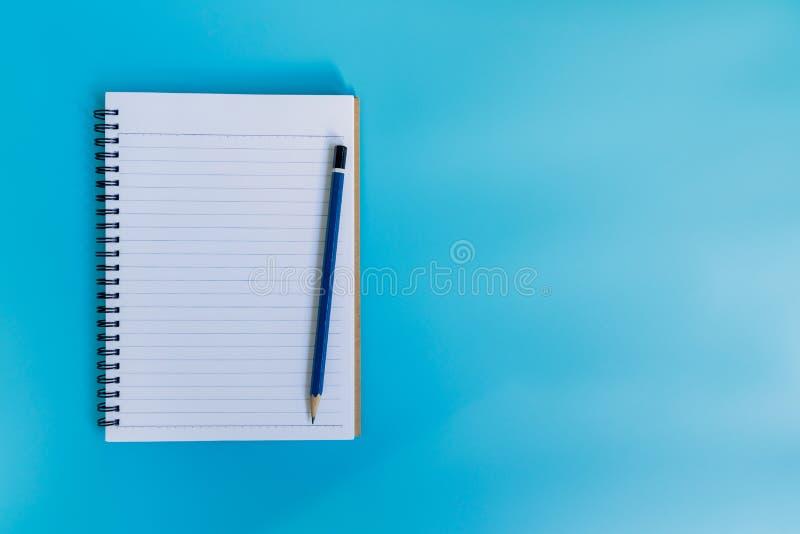 Odgórnego widoku notatnika papier na błękitnym pastelowego koloru tle z zdrojem fotografia royalty free