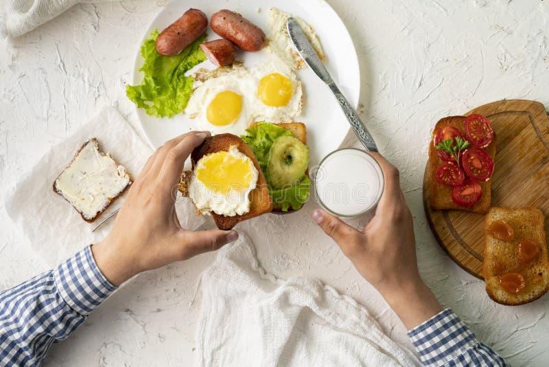 odgórnego widoku osoby łasowania śniadanie na białym stole, używać tableware, rozwidlenie i nóż, zdrowi posiłki obraz royalty free
