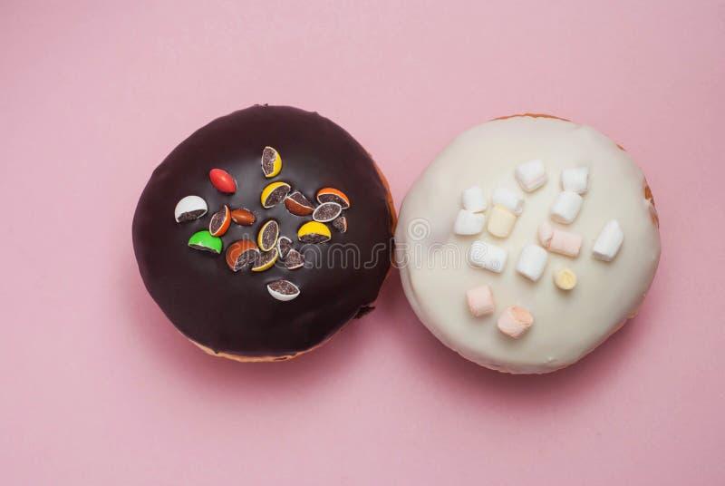 Odgórnego widoku pączki z Czekoladowym i Białym lodowaceniem na Pastelowych menchii tle Słodcy Deserowi Donuts z Odbitkową pastą zdjęcie royalty free