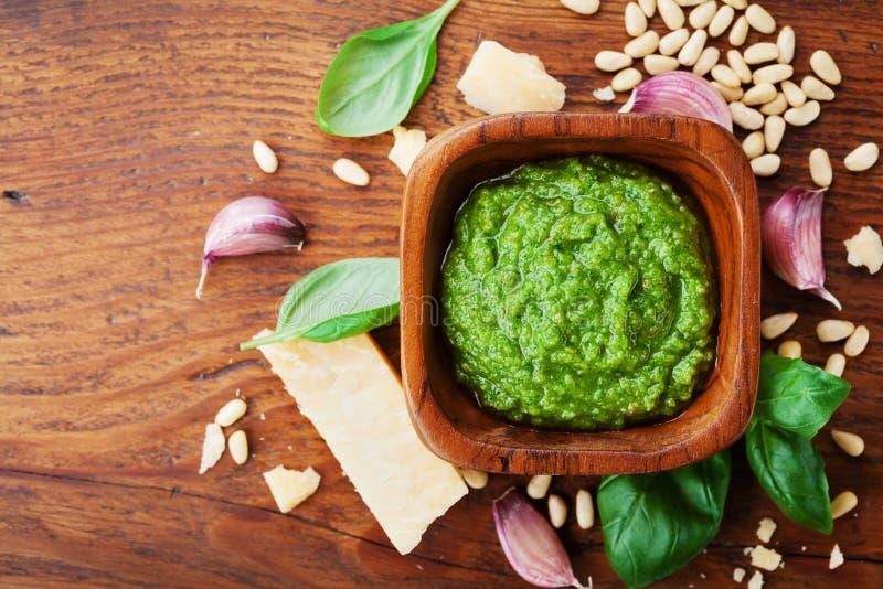 Odgórnego widoku pesto kumberland z basilem, sosnowymi dokrętkami, parmesan serem, czosnkiem i oliwa z oliwek na drewnianym stole fotografia royalty free