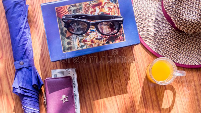 Odgórnego widoku plaży tło lato kobiety podróżuje akcesoria Okulary przeciwsłoneczni, pieniądze kiesa, książki, parasol, Słomiany zdjęcie royalty free