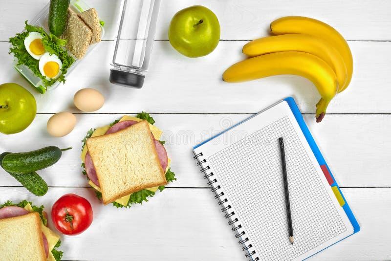 Odgórnego widoku planistyczny notatnik z kopii astronautyczną, zdrową śniadaniową kanapką z i, jajka, ogórek, pomidor fotografia royalty free
