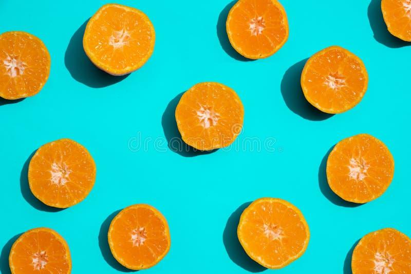 Odgórnego widoku pomarańcze świezi plasterki na jaskrawym błękitnym tle kosmos kopii Kreatywnie lata pojęcie Połówka cytrus w min zdjęcia stock