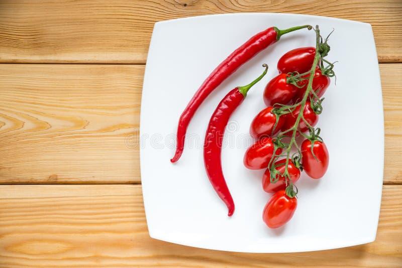 Odgórnego widoku pomidory, chłodny pieprz na drewnianym tle z copyspa fotografia stock