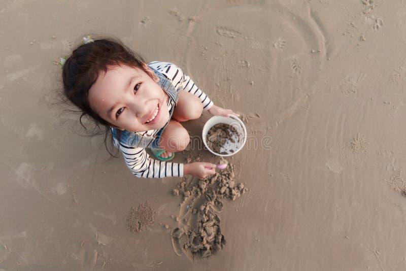 Odgórnego widoku portriat Azjatycka mała dziewczynka bawić się na piasek plaży wi zdjęcia royalty free