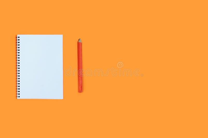 Odgórnego widoku pusty notatnik z ołówkiem na pomarańczowym tle Minimalna biurowego biurka miejsce pracy kosmos kopii flay nieatu zdjęcia royalty free