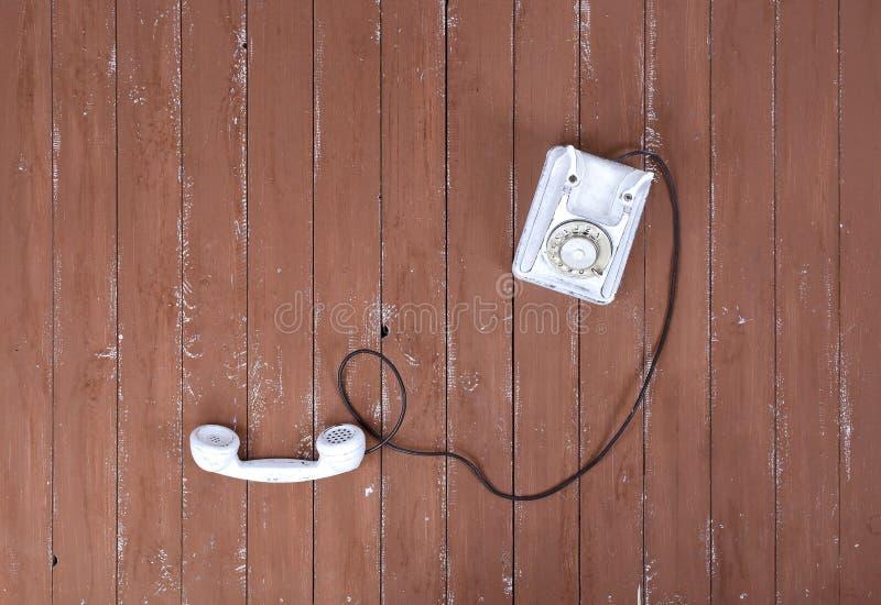 Odgórnego widoku rocznika biały telefon z w górę brązu drewna textured dalej obrazy royalty free