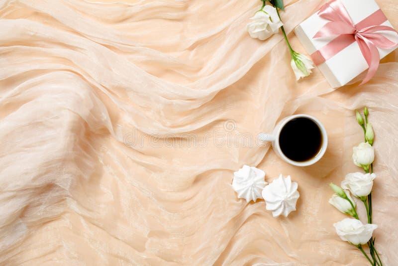 Odgórnego widoku romantyczny tło z ranek filiżanką, marshmallows, prezenta pudełko i wzrastał kwiaty Mieszkania nieatutowy kobiec zdjęcia stock
